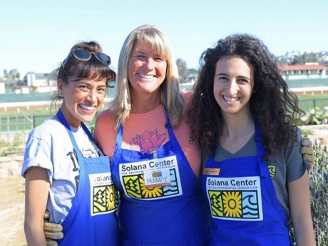 smiling volunteers in Solana Center aprons at the Del Mar Fairgrounds Infield Farm
